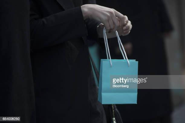 A shopper carries a Tiffany Co bag outside the company's flagship store on Fifth Avenue in New York US on Monday March 13 2017 Tiffany Co is...