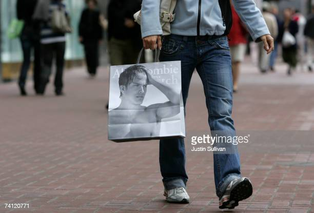 A shopper carries an Abercrombie and Fitch bag after leaving the store May 10 2007 in San Francisco California US retailers are reporting slumping...
