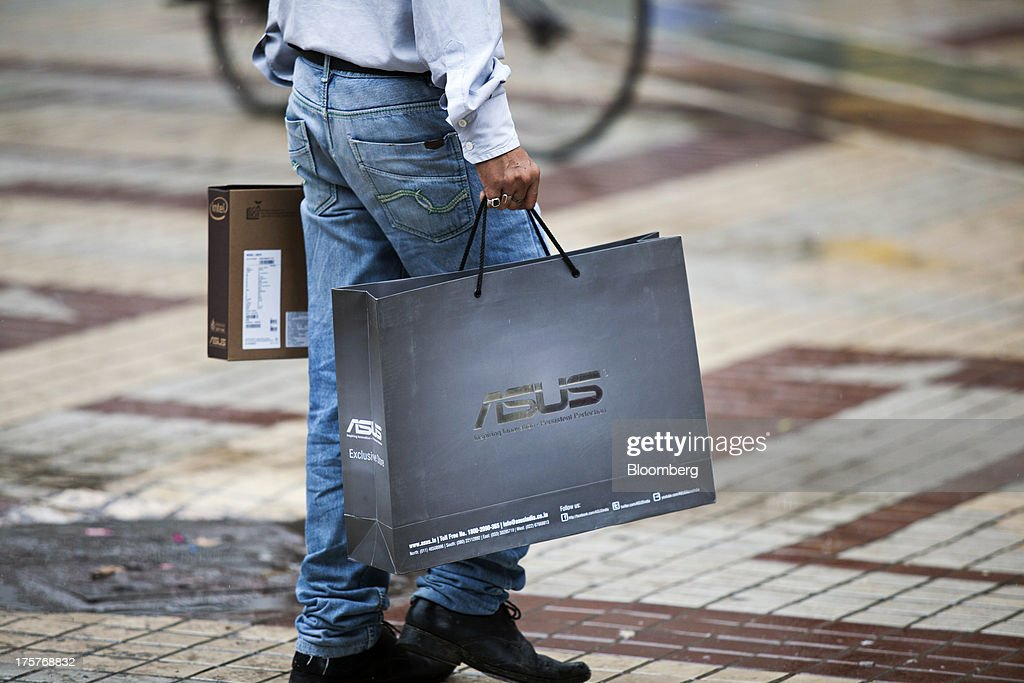 A shopper carries an Asustek Computer Inc.'s ASUS branded store bag in Nehru Place IT Market, a hub for the sale of electronic goods and computer accessories, in downtown New Delhi, India, on Wednesday, Aug. 7, 2013. India's consumer price index (CPI) figures for July are scheduled to be released on August 12. Photographer: Graham Crouch/Bloomberg via Getty Images