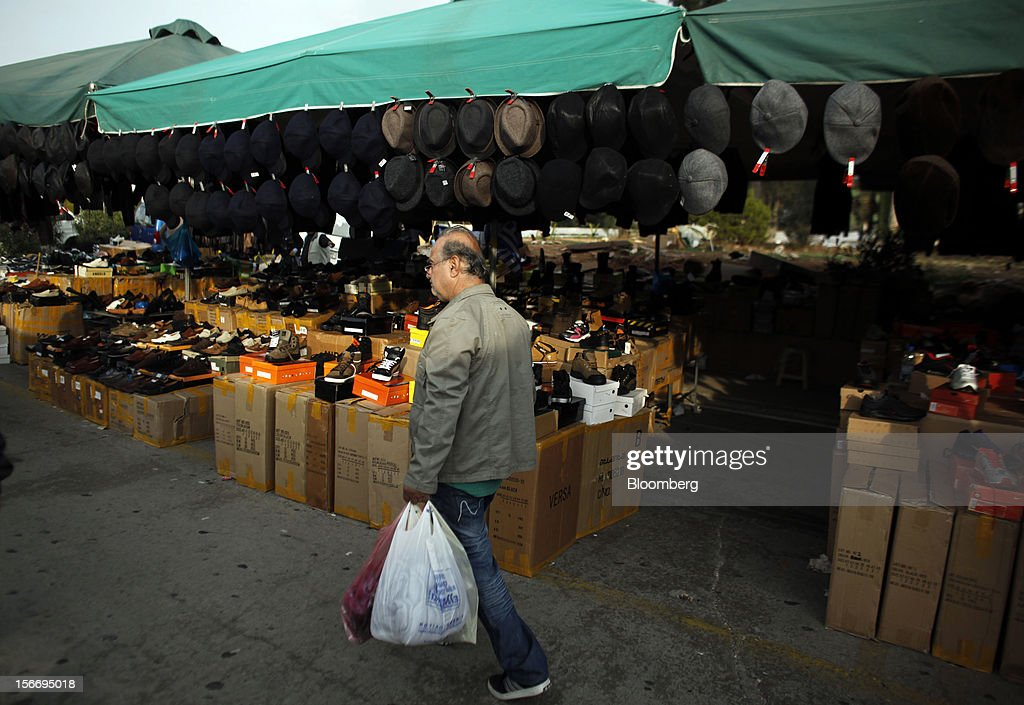 A shopper carries bags as he walks past a market stall selling shoes and hats at the 'Bazaar of Schisto' open market in Piraeus, Greece, on Sunday, Nov. 18, 2012. European finance ministers aim to stitch together Greece's next aid payment as a sputtering euro-area economy and a spat with the International Monetary Fund cloud efforts to resolve the debt crisis. Photographer: Kostas Tsironis/Bloomberg via Getty Images