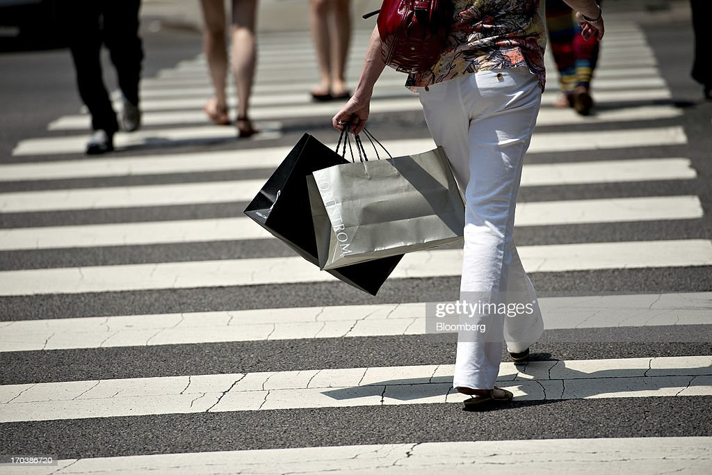 A shopper carries bags as she crosses the street in a retail area known as the 'Magnificent Mile' in Chicago, Illinois, U.S., on Tuesday, June 11, 2013. Sales at U.S. retailers probably rose in May as an improving job market gave consumers the confidence to shop for automobiles, home furnishings and clothing, economists said before reports this week. Photographer: Daniel Acker/Bloomberg via Getty Images