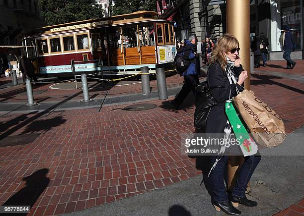 A shopper carries bags as she stands near a cable car turnaround in the Union Square shopping district January 14 2010 in San Francisco California...