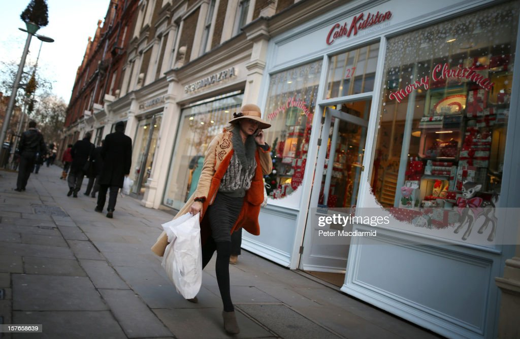 A shopper carries bags past shops along the King's Road in Chelsea on December 5, 2012 in London, England. The Chancellor of the Exchequer George Osborne has stated that the United Kingdom's economy is still struggling during his Autumn budget statement to Parliament.