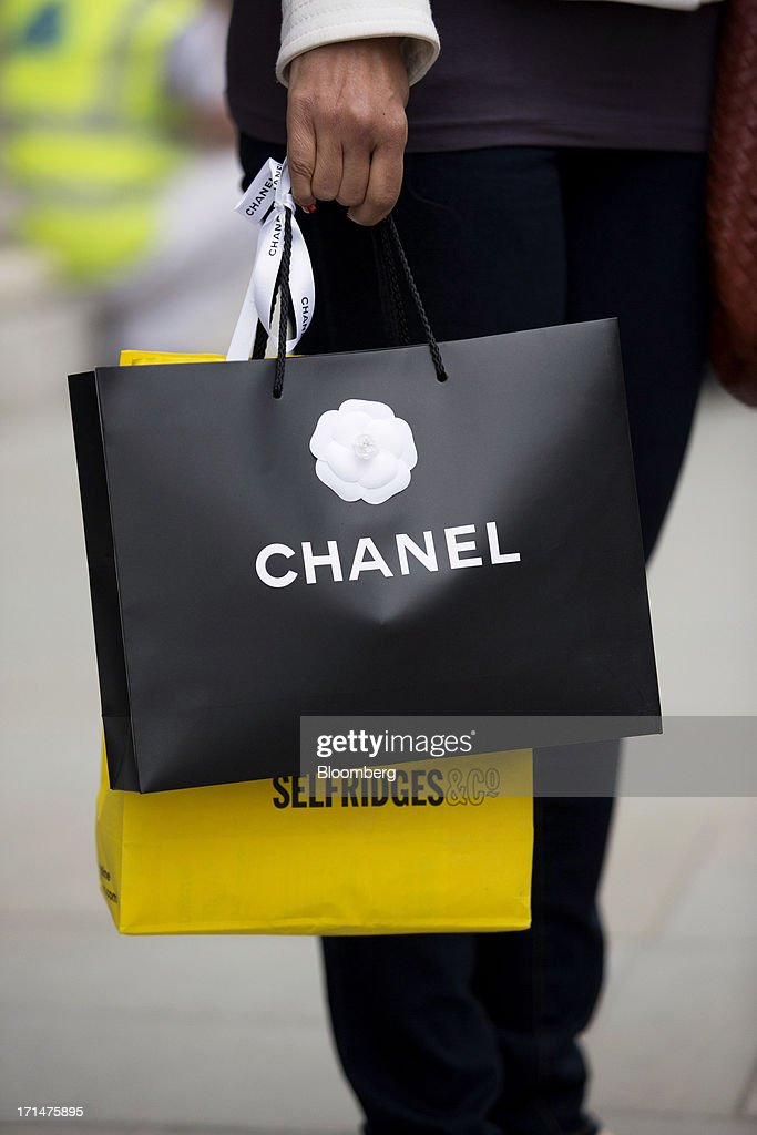 A shopper carries Chanel Inc. and Selfridges Plc branded carrier bags as they walk along Bond Street in London, U.K., on Monday, June 24, 2013. Bank of England Governor Mervyn King said the global economic recovery is at risk of further setbacks and central banks are a long way off tightening monetary policy. Photographer: Jason Alden/Bloomberg via Getty Images