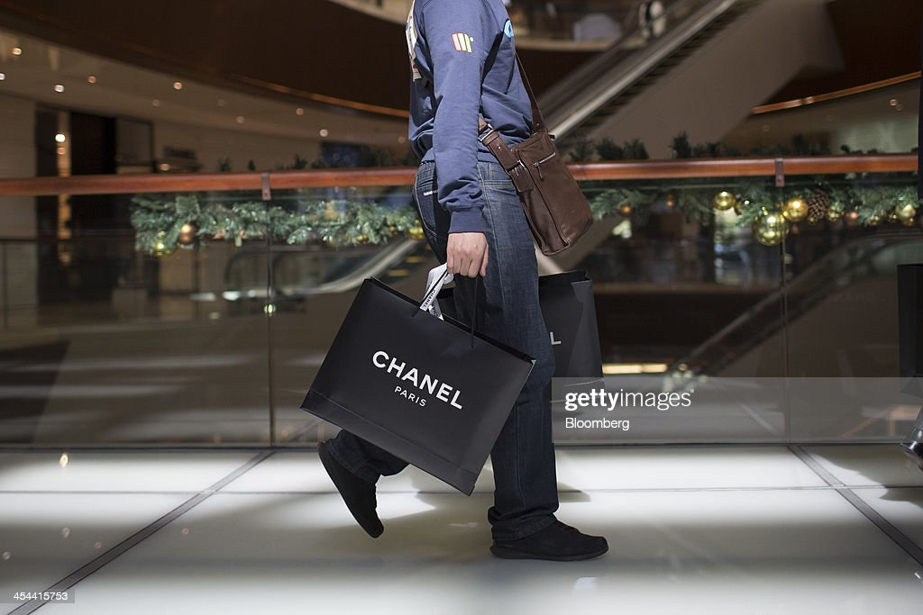 A shopper carries Chanel SA branded shopping bags at the TaiKoo Hui shopping mall, operated by Swire Properties Ltd., in Guangzhou, Guangdong province, China, on Saturday, Nov. 30, 2013. China's government may set its 2014 growth target at 7 percent, the Economic Information Daily reported on Dec. 3, citing the State Information Center. This compares with a goal of 7.5 percent for this year. Photographer: Brent Lewin/Bloomberg via Getty Images