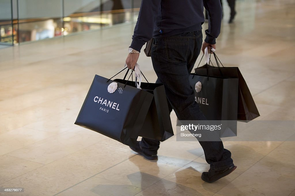 A shopper carries Chanel SA branded shopping bags inside the TaiKoo Hui shopping mall, operated by Swire Properties Ltd., in Guangzhou, China, on Saturday, Nov. 30, 2013. China's government may set its 2014 growth target at 7 percent, the Economic Information Daily reported on Dec. 3, citing the State Information Center. This compares with a goal of 7.5 percent for this year. Photographer: Brent Lewin/Bloomberg via Getty Images