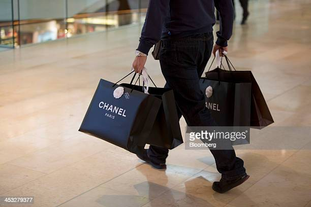 A shopper carries Chanel SA branded shopping bags inside the TaiKoo Hui shopping mall operated by Swire Properties Ltd in Guangzhou China on Saturday...