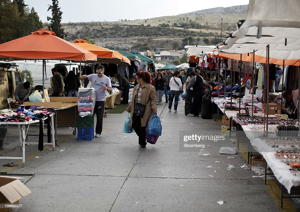 A shopper carries her bags past market stalls at the at the 'Bazaar of Schisto' open market in Piraeus, Greece, on Sunday, Nov. 18, 2012. European finance ministers aim to stitch together Greece's next aid payment as a sputtering euro-area economy and a spat with the International Monetary Fund cloud efforts to resolve the debt crisis. Photographer: Kostas Tsironis/Bloomberg via Getty Images
