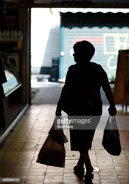 A shopper carries her purchases in plastic bags as she browses stalls at an indoor market in Rome Italy on Tuesday Aug 12 2014 Italy's economy shrank...