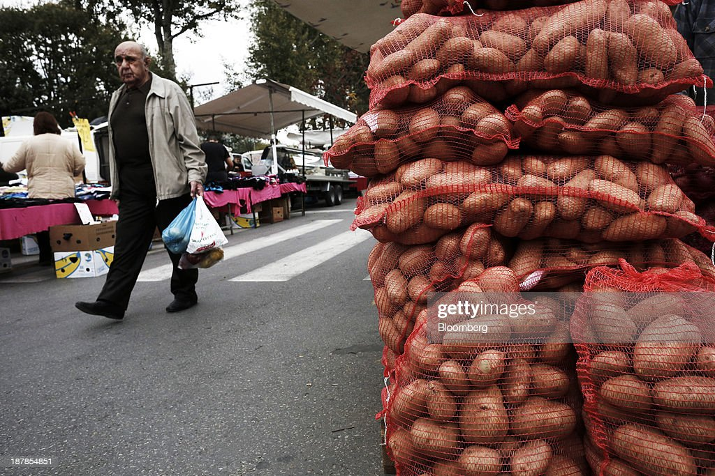 A shopper carries his shopping past sacks of potatoes for sale at a farmer's market in the Toumpa district of Thessaloniki, Greece, on Wednesday, Nov. 13, 2013. Greece 'is following a fiscal adjustment program that aims to make the country's public finances sustainable on a permanent basis,' Finance Minister Yannis Stournaras told lawmakers during the debate, after holding talks with the troika earlier in the week. Photographer: Konstantinos Tsakalidis/Bloomberg via Getty Images