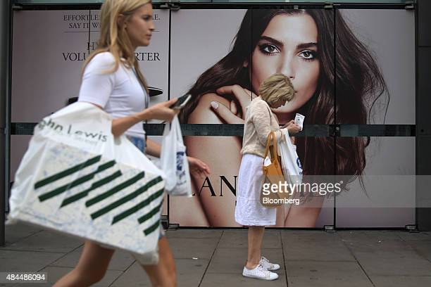 A shopper carrying a John Lewis Plc bag passes a Lancome Parfums Et Beaute Et Compagnie SNC advertisement in the window of Boots store operated by...