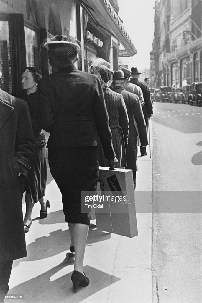 A shopper carrying a package from the Lillywhites shop Bond Street London May 1939 Original publication Picture Post 67 Bond Street pub 20th May 1939