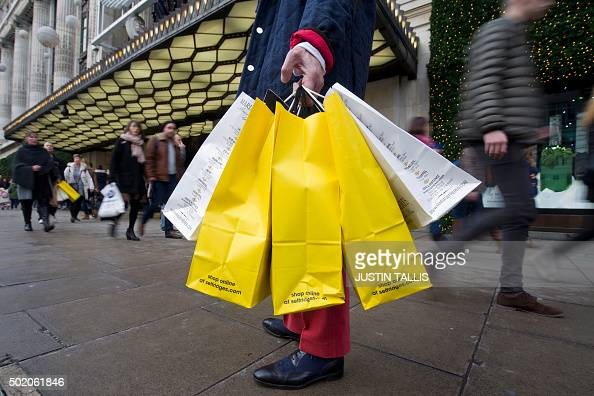 A shopper carrying bags waits outside Selfridges on Oxford Street one of the main shopping streets in central London on December 20 on the final...
