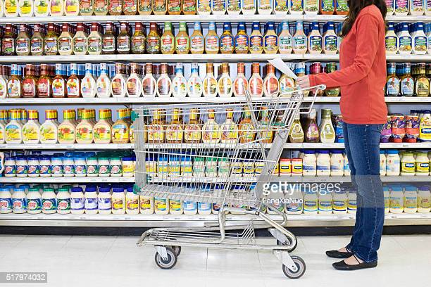 Shopper checking list in supermarket aisle
