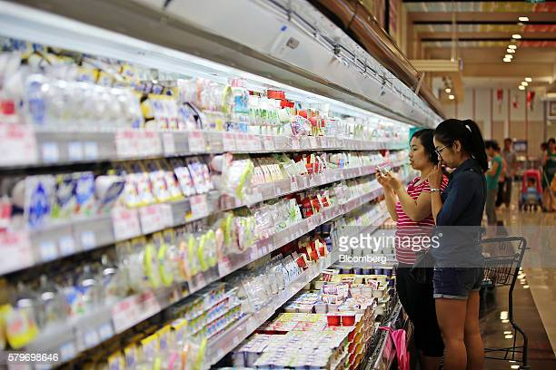 A shopper checks a yogurt carton at the Aeon Co mall in the Long Bien district of Hanoi Vietnam on Thursday July 21 2016 With a young population an...