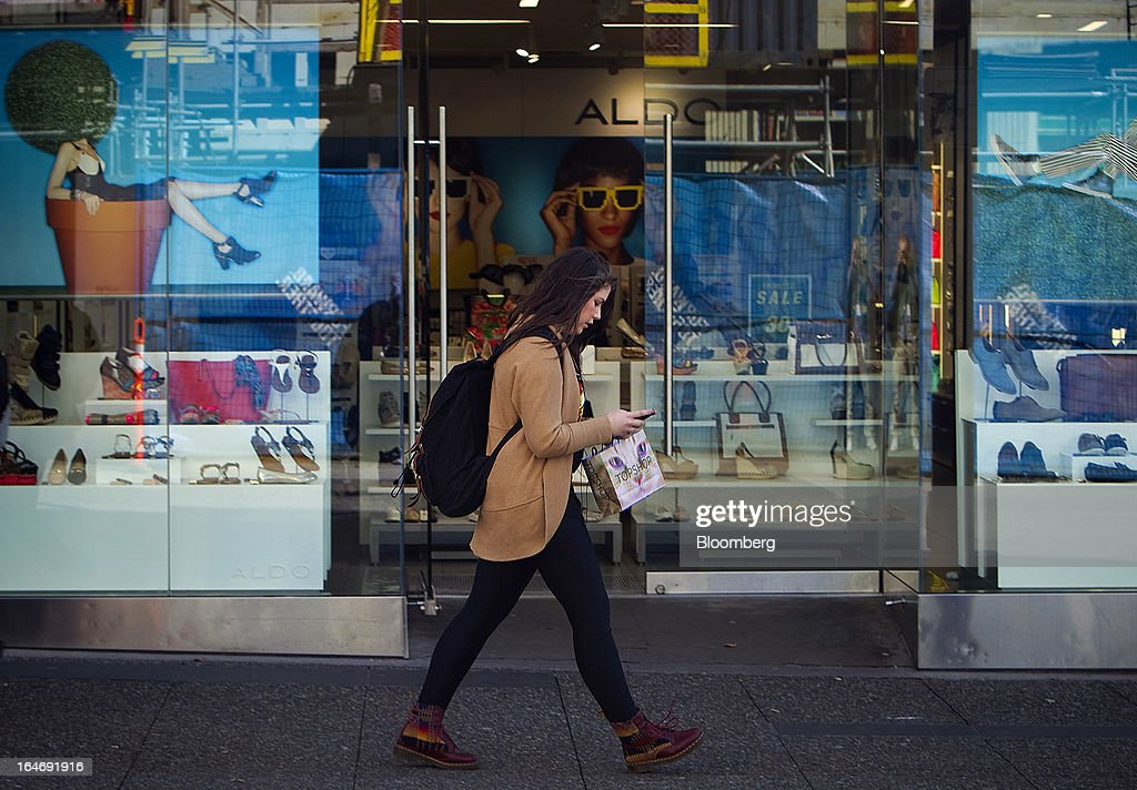 A shopper checks her phone while passing in front of an Aldo Group Inc. store on Robson St. in Vancouver, British Columbia, Canada, on Monday, March 25, 2013. Statistics Canada (STCA) is scheduled to release consumer price index data on March 27, 2013. Photographer: Ben Nelms/Bloomberg via Getty Images