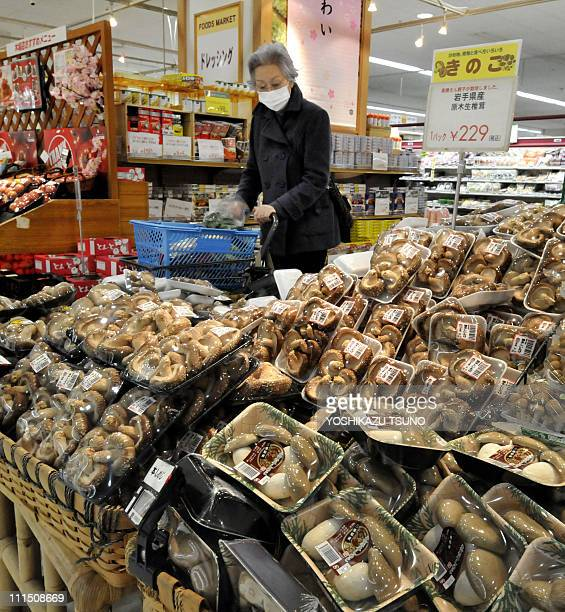 A shopper checks packs of mushrooms at a supermarket in Tokyo on April 4 2011 after the government ordered a halt to shipments of shiitake mushrooms...