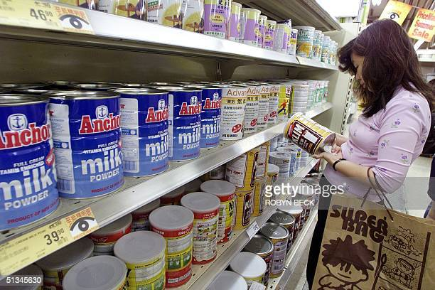 A shopper checks the label for the country of origin on a milk formula in a Hong Kong supermarket 08 June 1999 Hong Kong has extended its ban on pork...