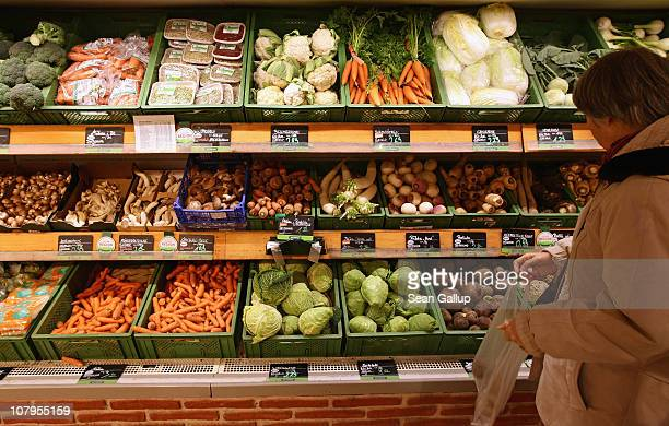 A shopper chooses from organic vegetables at a branch of German organic grocery store chain Bio Company on January 10 2011 in Berlin Germany Organic...