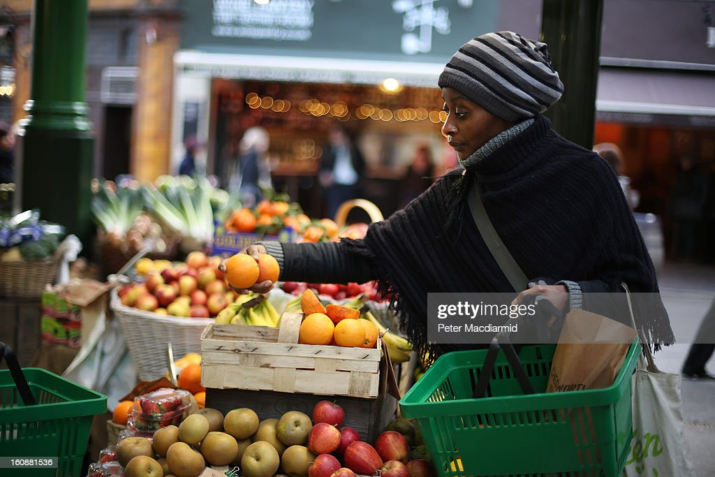 A shopper chooses some oranges from a stall at Borough Market on February 7, 2013 in London, England. Borough Market, London's oldest since 1756, has recently completed renovation and today had it's first day of full trading.