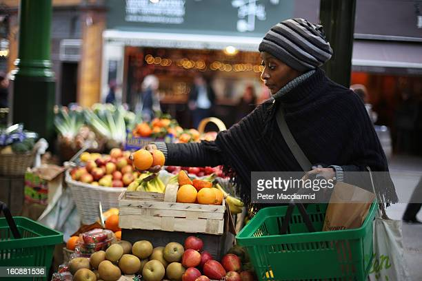 A shopper chooses some oranges from a stall at Borough Market on February 7 2013 in London England Borough Market London's oldest since 1756 has...