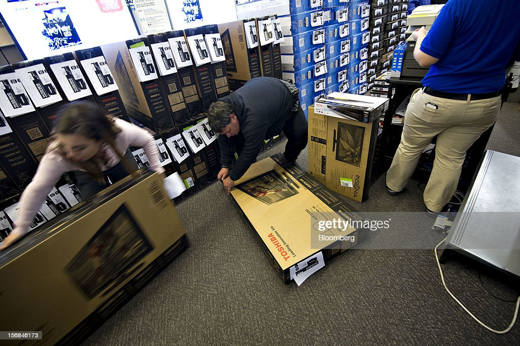 Shopper Chris Ashley prepares to pay for two flat screen televisions and a blue-ray DVD player, after waiting in line outside the store for 29 hours, at a Best Buy Co. store in Peoria, Illinois, U.S., on Friday, Nov. 23, 2012. Discount store shoppers are prepared to wait in long lines on Black Friday, though they are skeptical about whether they'll get the best deals of the season. Photographer: Daniel Acker/Bloomberg via Getty Images