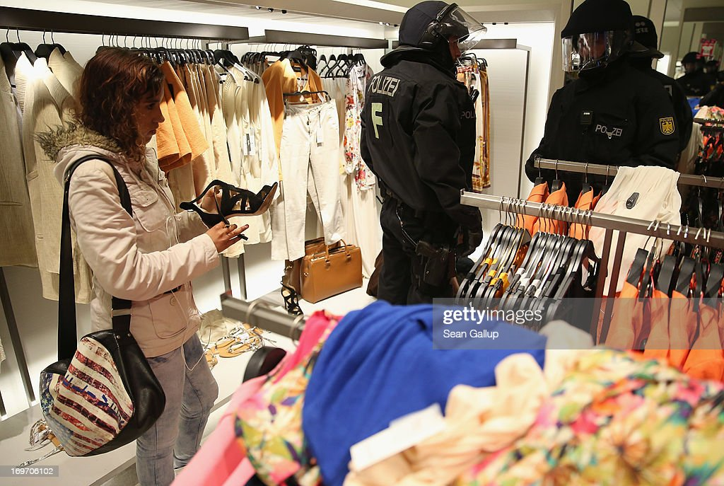 A shopper considers a shoe as riot police question a young man who had been among Blockupy protesters who had stormed into a Zara clothing store in the Zeil pedestrian shopping street on May 31, 2013 in Frankfurt am Main, Germany. Several thousand protesters are taking part in Blockupy protests today and tomorrow in Frankfurt in order to demonstrate aginst ECB debt policy, food prices speculation by Deutsche Bank and the labor practices inherent in the discount clothing industry.