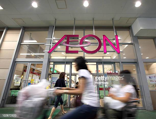 A shopper cycles past an Aeon Co shopping center in Tokyo Japan on Wednesday July 7 2010 Aeon Co will book a gain of 181billion yen in the fiscal...