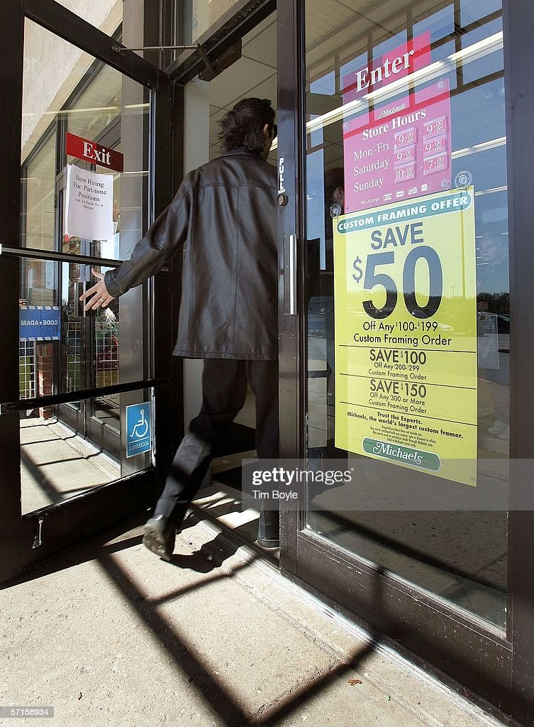 a shopper enters a michaels store past a sign for a custom framing sale march