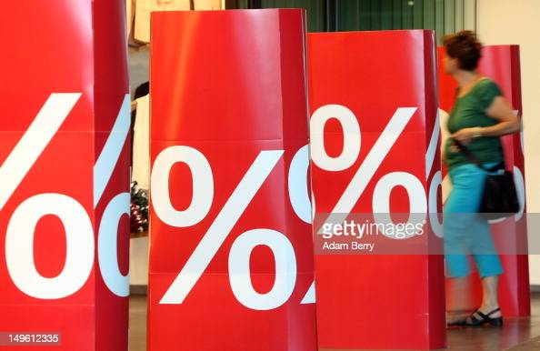 A shopper enters a store advertising summer sales on August 1 2012 in Berlin Germany German retailers began their annual summer clearance sale on...