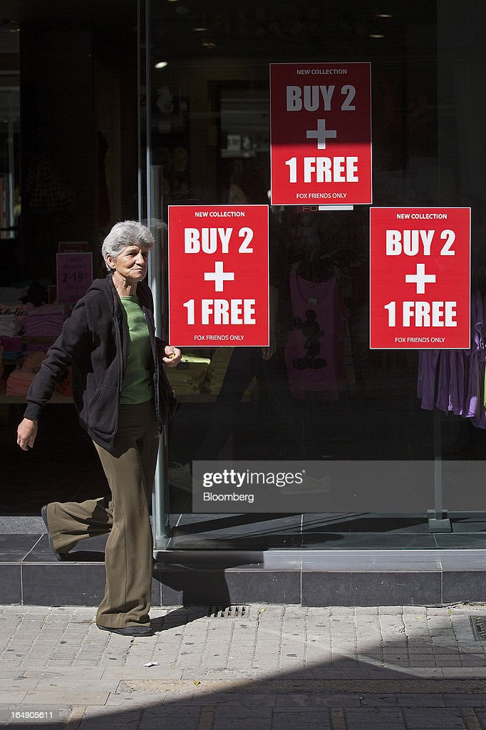 A shopper exits a clothing store advertising a 'Buy 2, Get 1 Free' promotion in it's window display on Ledra Street in Nicosia, Cyprus, on Friday, March 29, 2013. Cypriots face a second day of bank controls over their use of the euro as officials in Europe urged the country to move quickly to lift the restrictions, the first time they have been imposed on the common currency. Photographer: Simon Dawson/Bloomberg via Getty Images