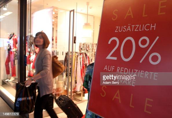 A shopper exits a store advertising summer sales on August 1 2012 in Berlin Germany German retailers began their annual summer clearance sale on...