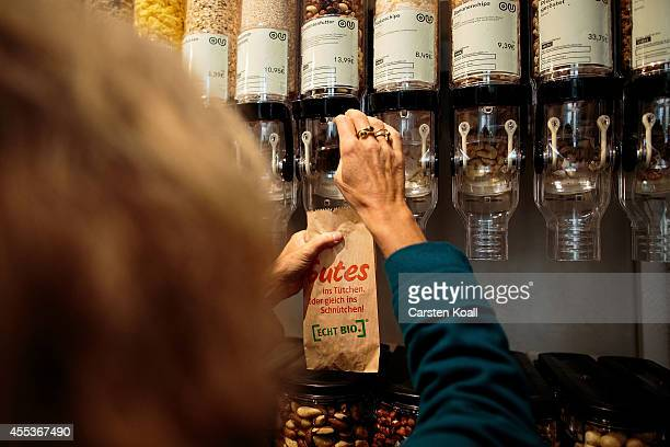 A shopper fills a small paper bag showing the companylogo with nuts at the 'Original Unverpackt' supermarket on the store's opening day on September...