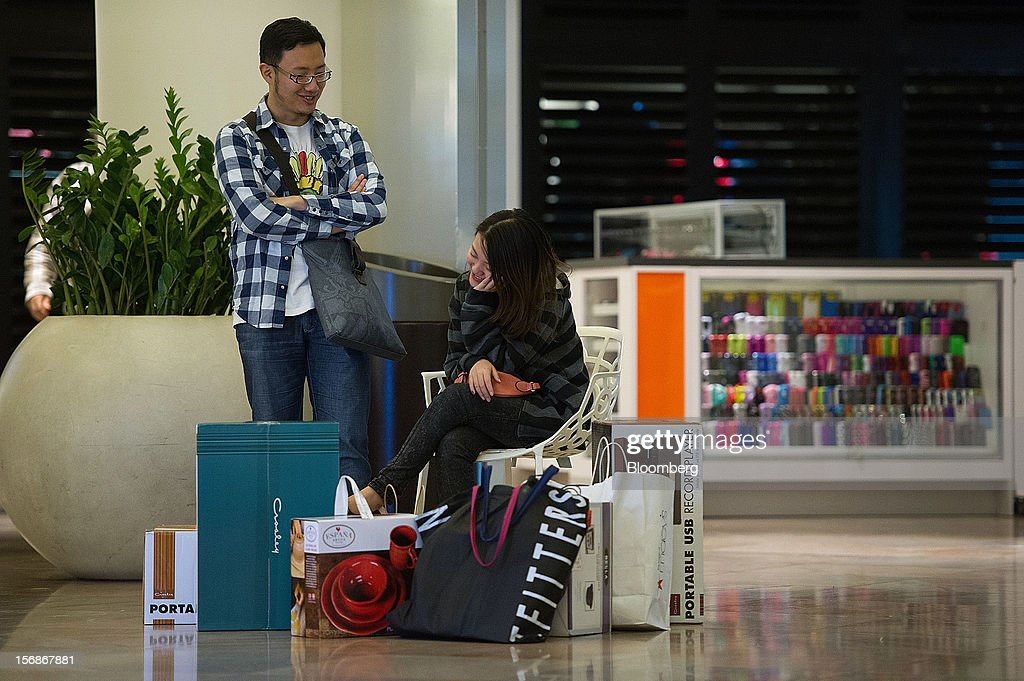 Shopper Frank Huang, left, and Diana Wang take a break from shopping at the Westfield San Francisco Centre mall in San Francisco, California, U.S., on Friday, Nov. 23, 2012. To get shoppers to spend more than last year, retailers have continued to turn Black Friday, originally a one-day event after Thanksgiving, into a week's worth of deals and discounts. Photographer: David Paul Morris/Bloomberg via Getty Images