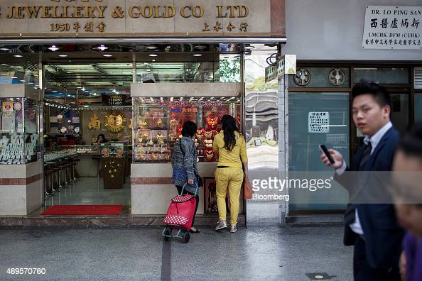 A shopper holding a shopping cart browses gold jewelry in the window of a jewelry store in the Sheung Shui district near the border with mainland...