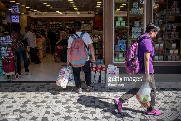 A shopper holding baby diapers stands outside a pharmacy store in the Sheung Shui district near the border with mainland China in Hong Kong China on...