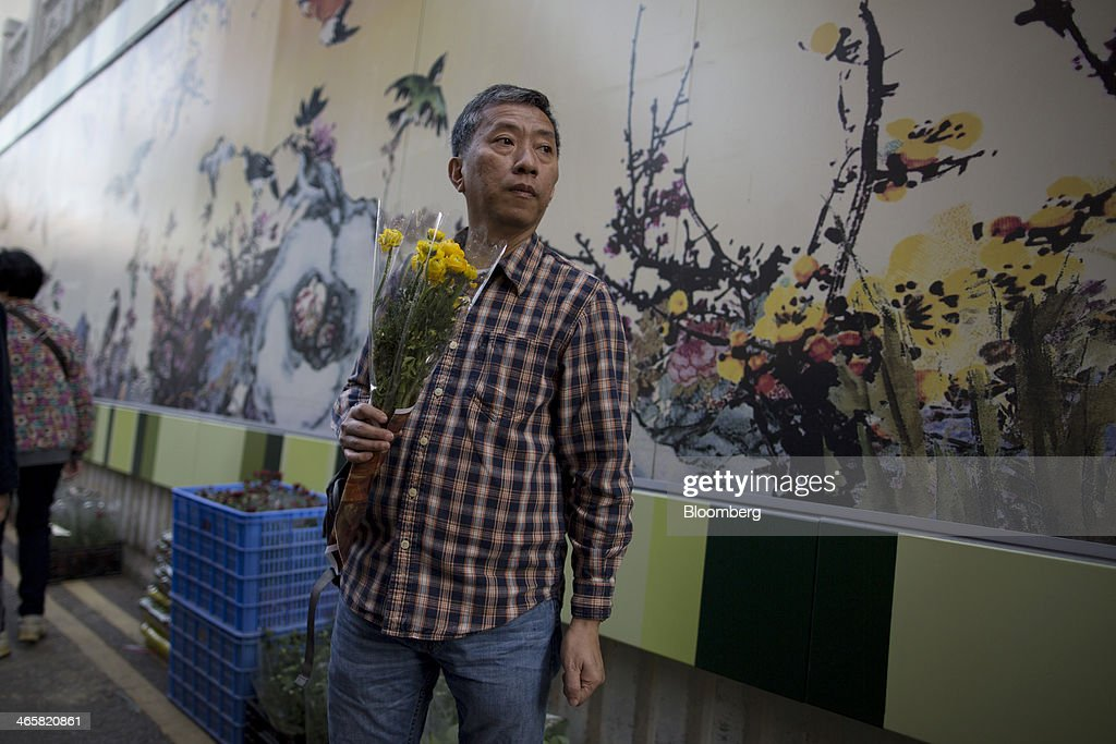 A shopper holds a bunch of flowers at a flower market in the Mongkok district of Hong Kong, China, on Wednesday, Jan. 29, 2014. The citys financial markets will close early on Jan. 30 for the Chinese New Year holidays and resume trading on Feb. 4, while those in the mainland will be shut from tomorrow through Feb. 6. Photographer: Brent Lewin/Bloomberg via Getty Images