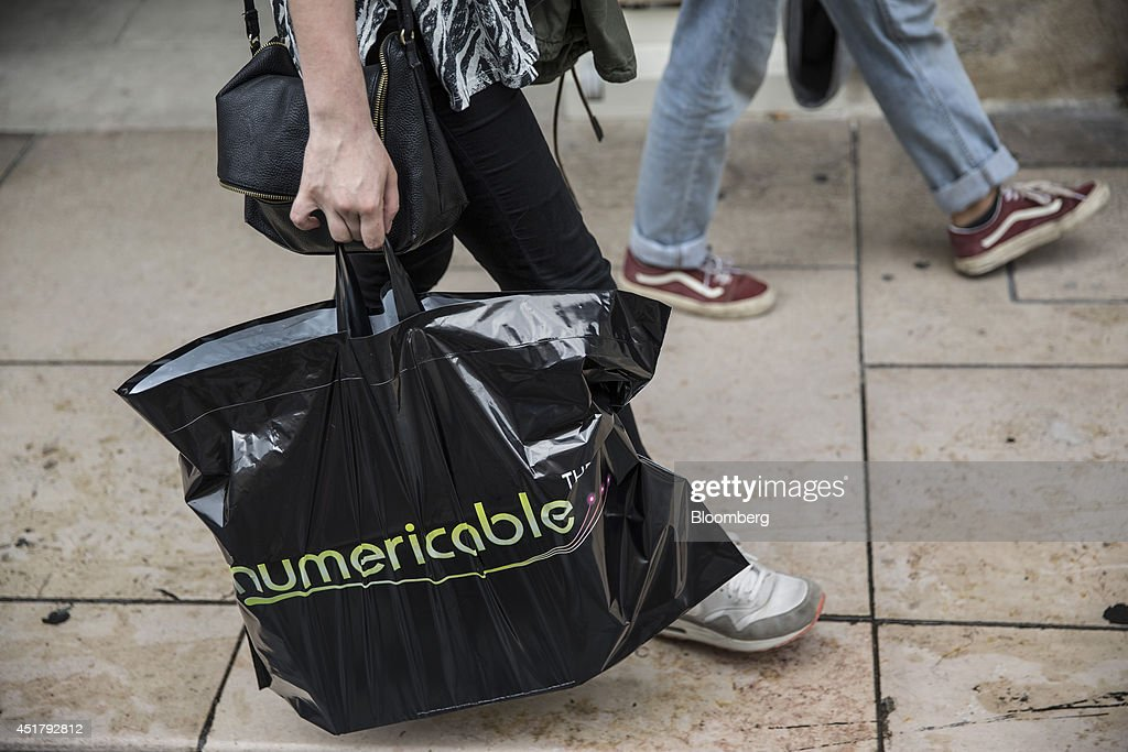 A shopper holds a Numericable Group SA branded carrier bag in Bordeaux, France, on Friday, July 4, 2014. Altice SA is raising its stake in Numericable after agreeing in April to merge the French cable provider with Vivendi SA's phone unit SFR, a transaction valued at more than 17 billion euros. Photographer: Balint Porneczi/Bloomberg via Getty Images