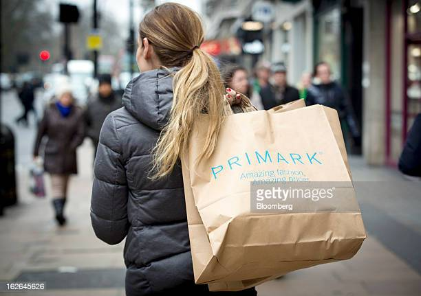 A shopper holds a Primark shopping bags while waiting for a bus along Oxford Street the store is operated by Associated British Foods Plc in central...