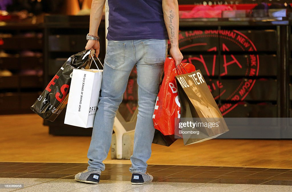 A shopper holds branded bags from Office Holdings Ltd. and Hollister Co. stores as he looks inside a retail outlet at the Manchester Arndale shopping centre in Manchester, U.K., on Thursday, Sept. 3, 2013. U.K. consumer confidence rose to the highest in almost six years in September as signs of a sustainable economic recovery spurred consumers to spend. Photographer: Paul Thomas/Bloomberg via Getty Images