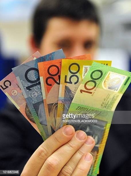 A shopper holds the full array of Australian dollar polymer notes as investors continue to sell down the local currency in Sydney on June 7 2010 The...