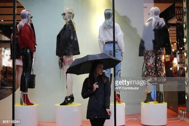 A shopper huddles under an umbrella as rain fell in central London on August 9 2017 / AFP PHOTO / Tolga AKMEN