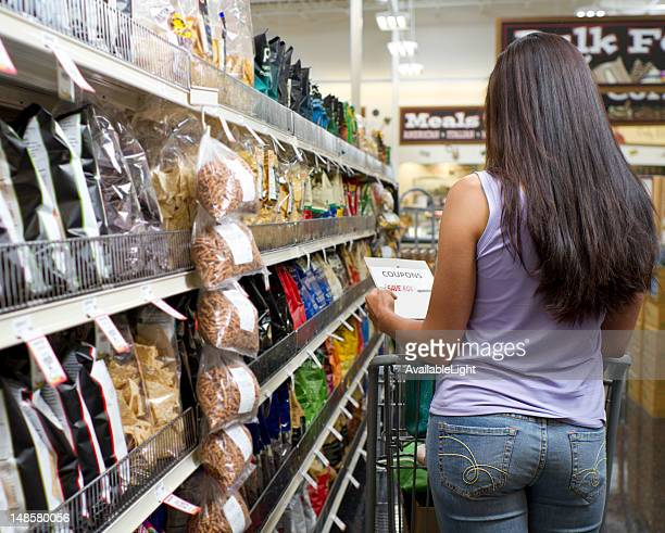 Shopper in Store Looks at Coupon