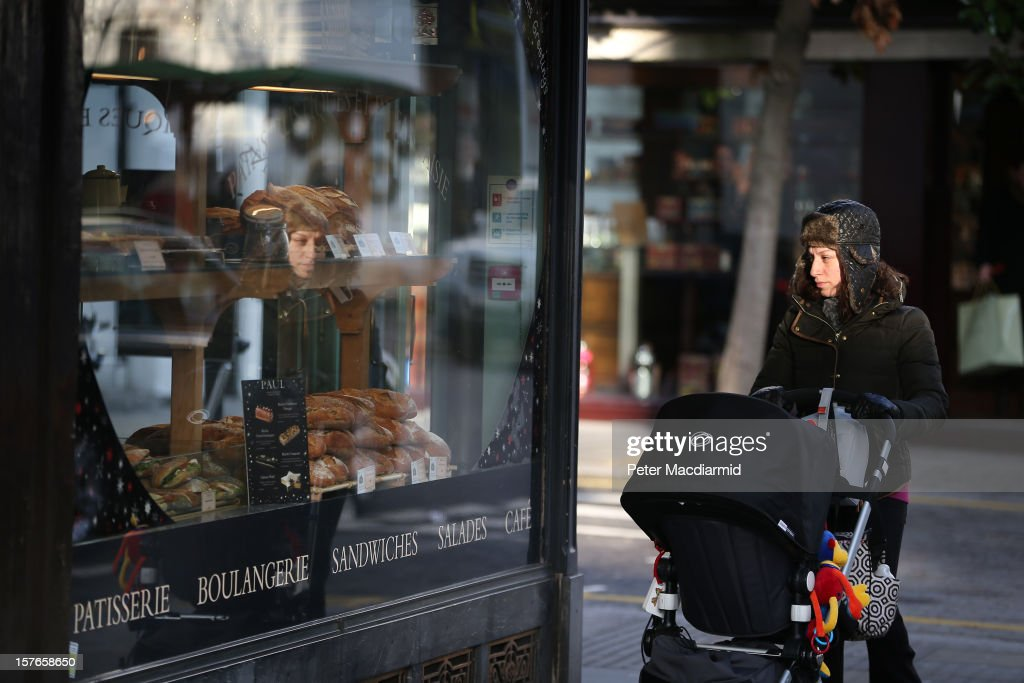 A shopper is reflected in a shop window in the King's Road in Chelsea on December 5, 2012 in London, England. The Chancellor of the Exchequer George Osborne has stated that the United Kingdom's economy is still struggling during his Autumn budget statement to Parliament.