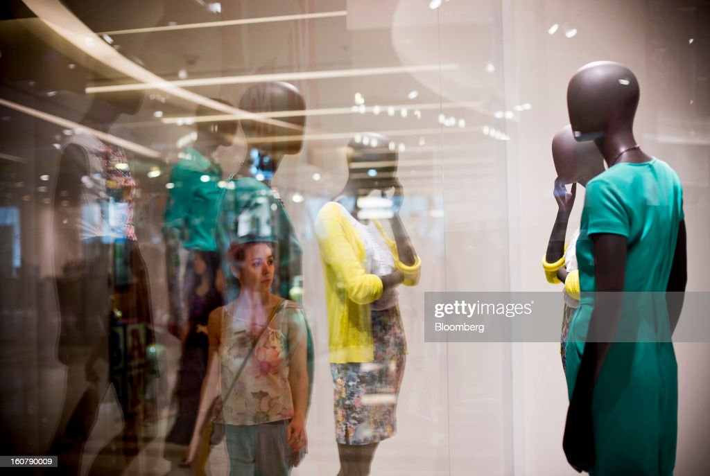 A shopper is reflected in a window display of mannequins inside the Siam Paragon shopping mall in Bangkok, Thailand, on Tuesday, Feb. 5, 2013. Thai inflation may average 2.8 percent this year, the Bank of Thailand said. Photographer: Brent Lewin/Bloomberg via Getty Images