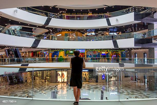 A shopper is resting beside the circle railing in the center of Tongzhou Wanda department store newly opened at the end of 2014 Dalian Wanda Group Co...