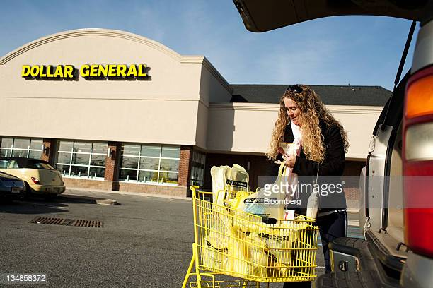 Shopper Karen Brown puts her purchases in the back of her vehicle at a Dollar General Corp store in Saddle Brook New Jersey US on Saturday Dec 3 2011...