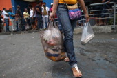 A shopper leaves a supermarket with groceries as others wait in line on March 2 2014 in Caracas Venezuela Venezuela has one of the highest inflation...