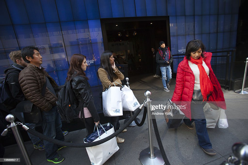 A shopper leaves Hollister on Fifth Avenue as people wait to enter the store during the Black Friday sales on November 23, 2012 in New York City. Shoppers filled stores in search of the many potential bargains on offer during the traditional yearly sale, which got its name as it's said to put retailers 'in the black,' or making a profit.