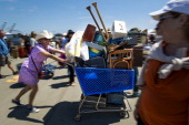 Shopper Liz Capron of Fairfax California pushes a shopping cart with items she purchased at the Alameda Point Antiques Faire in Alameda California US...